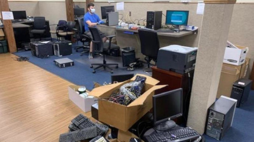 The BTS office filled with donated computers, as one worker is preparing one of the computer