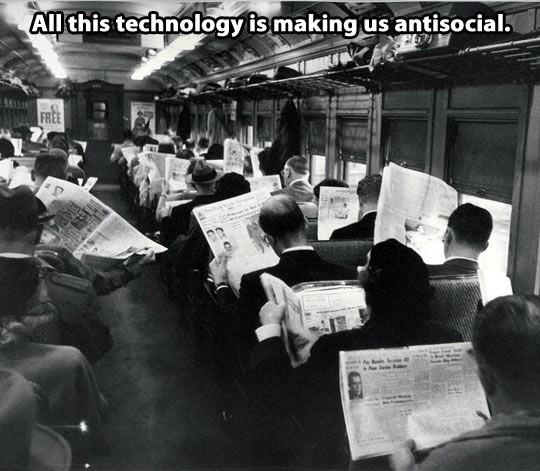 Black and white photograph showing a train full of people reading newspapers