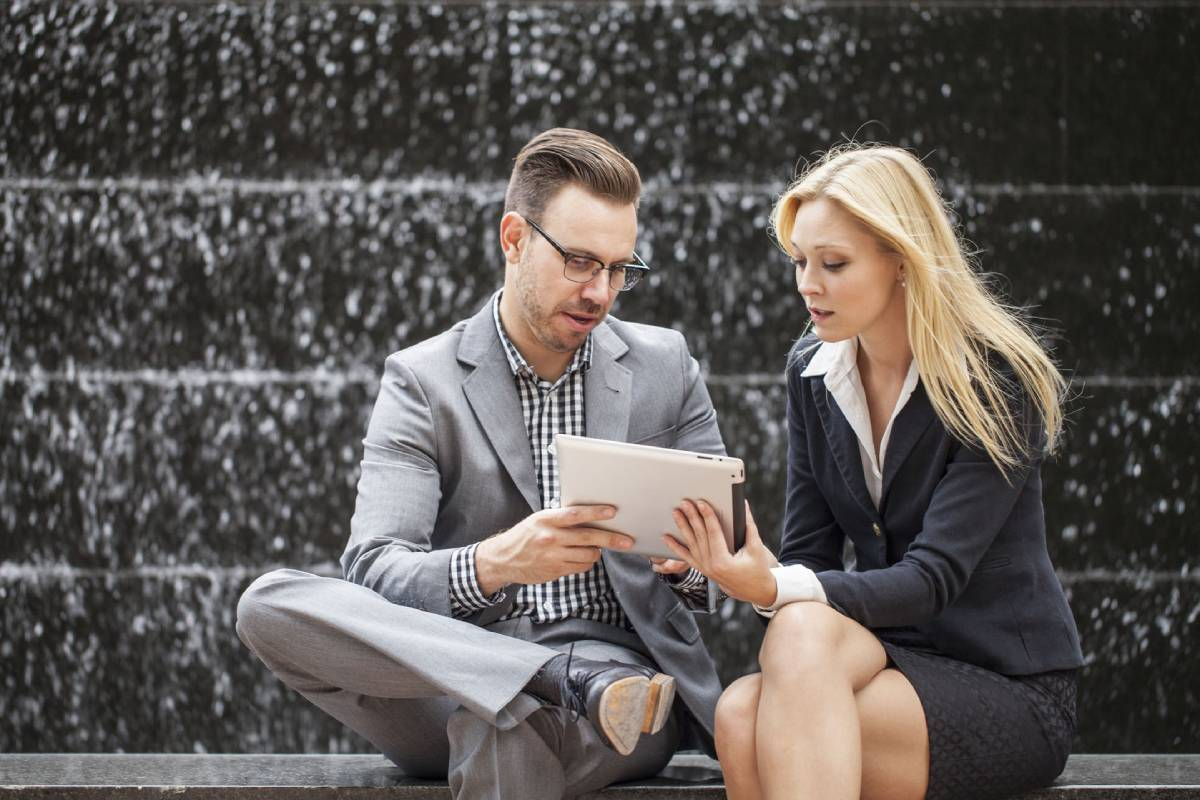 Businessman and woman collaborating using a tablet