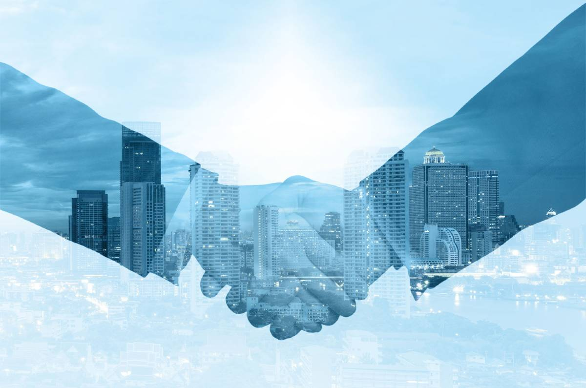 Businessmen shaking hands on a faded blue city skyline background
