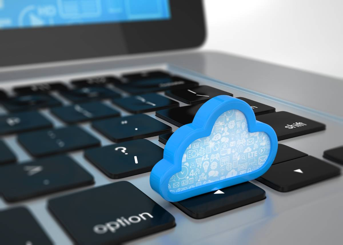 A blue cloud sitting on the directional keys of a laptop